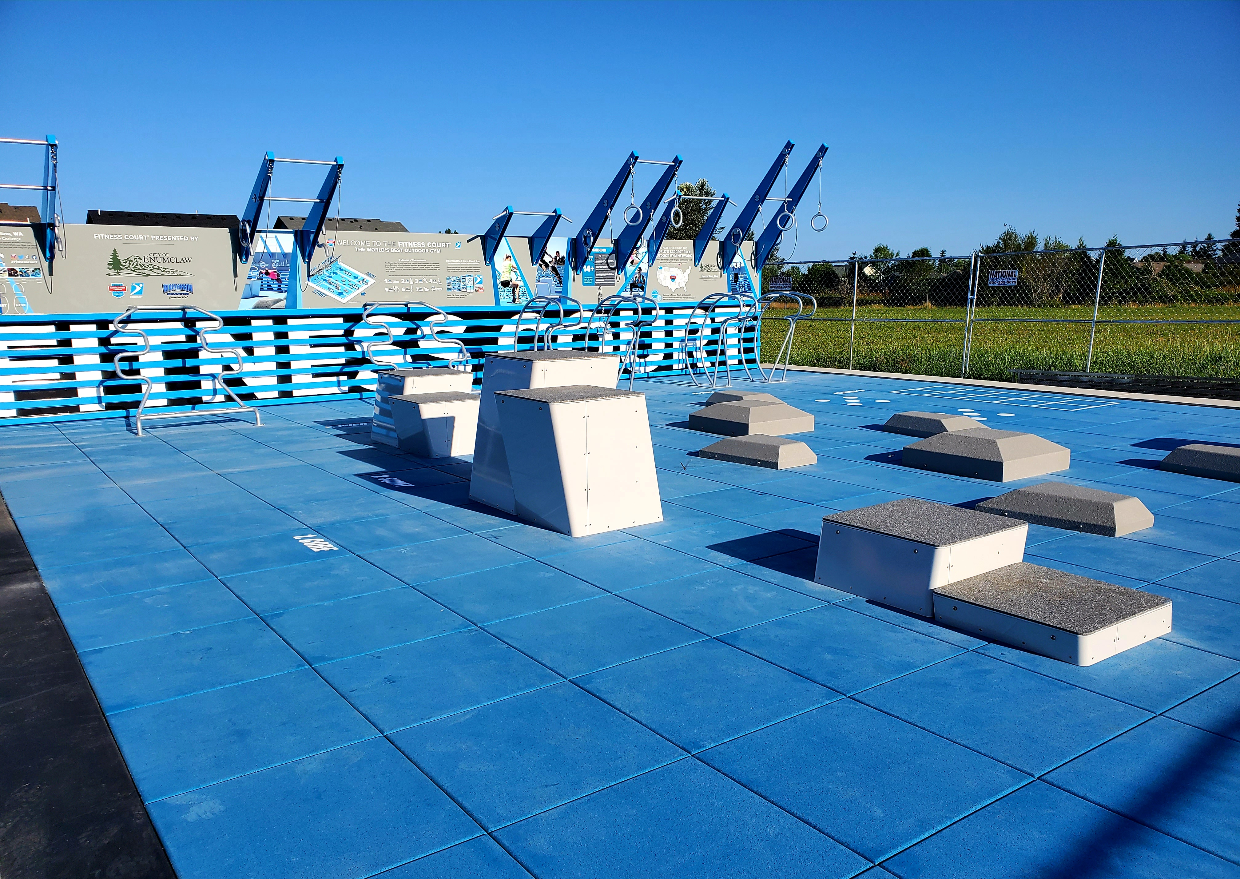 Outdoor fitness court featuring metal bars and rings, as well as concrete platforms of various heights