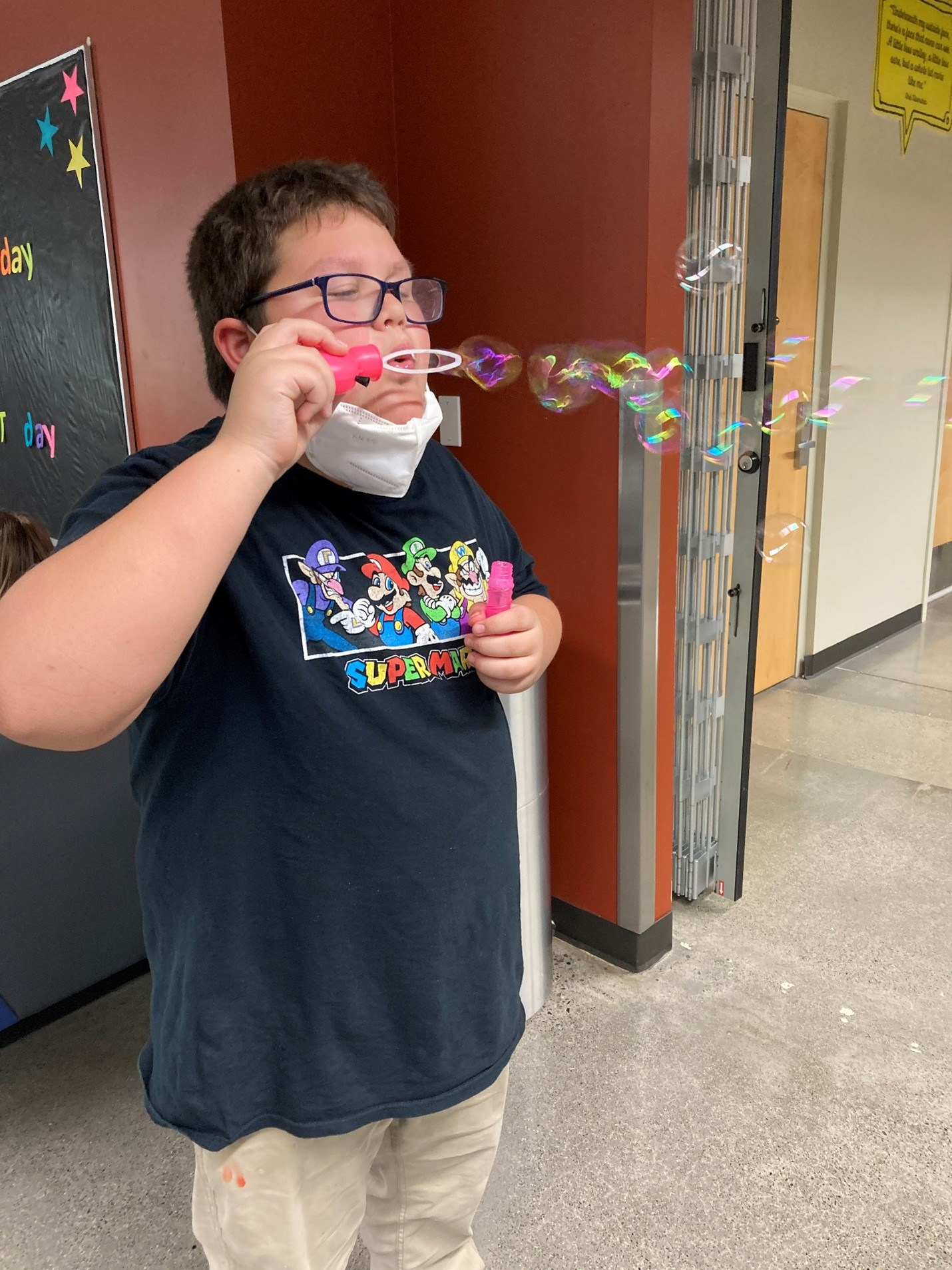 Photo of a kid blowing bubbles with their mask down