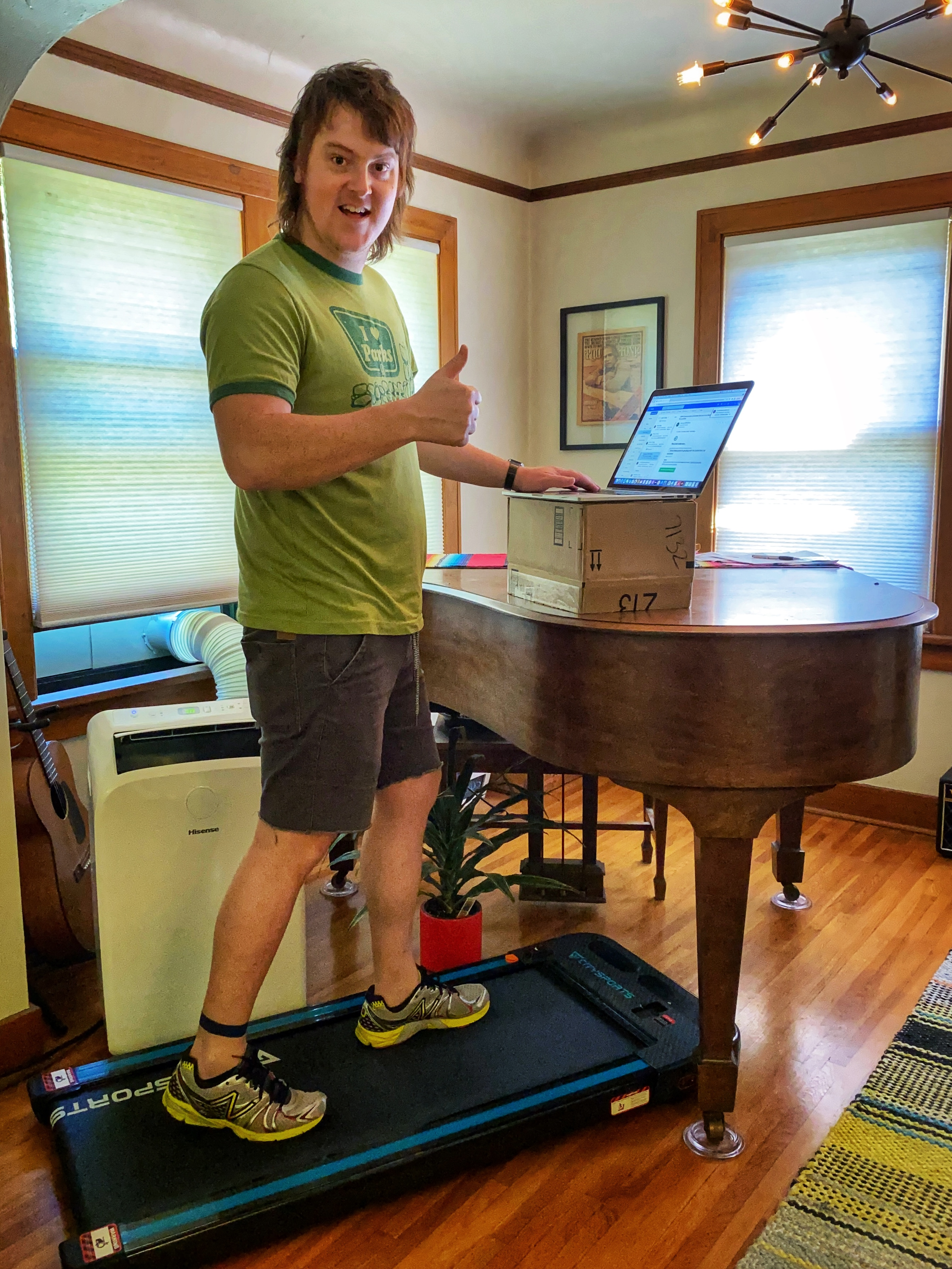 Josh Morrisey on his homemade treadmill desk with a computer propped up on a piano