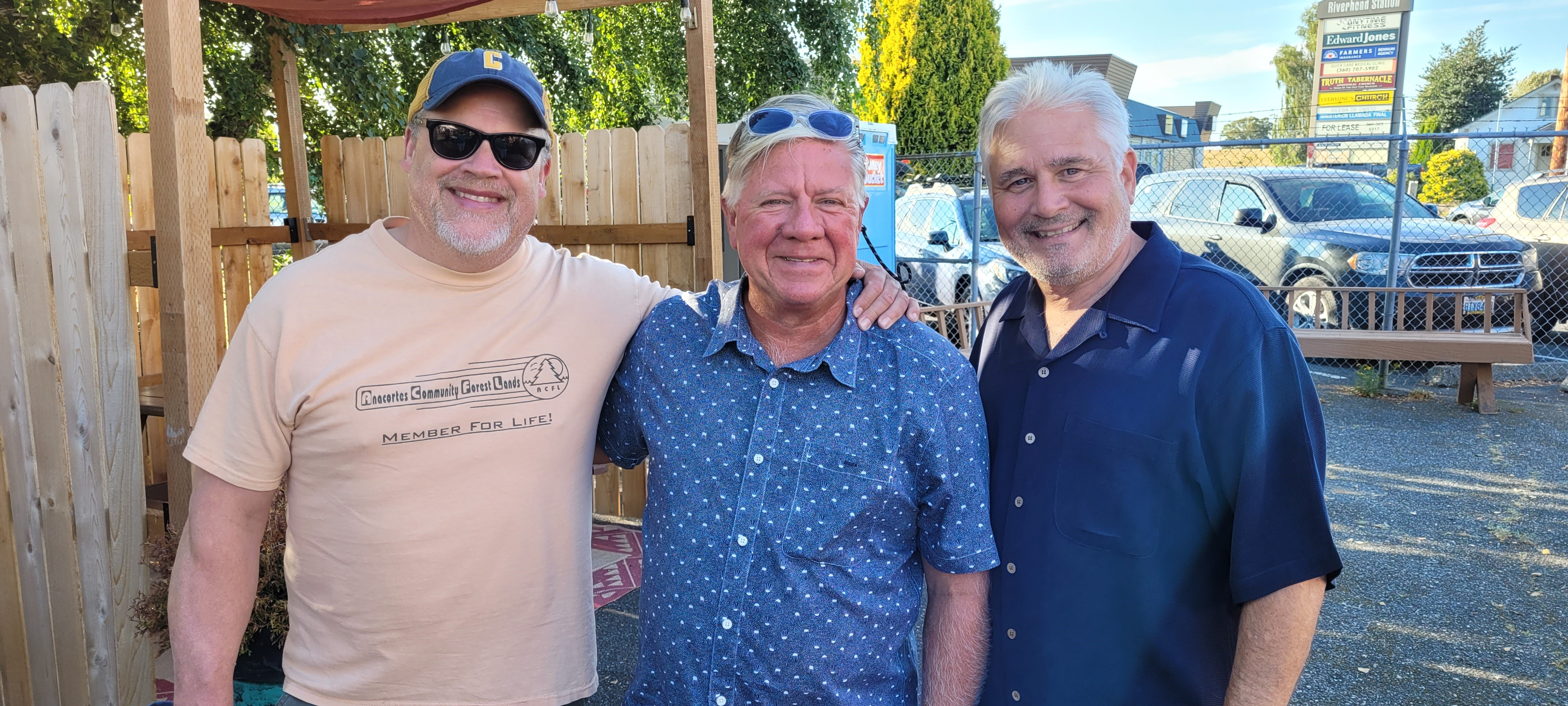 Three men standing together in front of a wooden fence. One is wearing a pale orange shirt, sunglasses, and a baseball cap. One is wearing a blue button down shirt and has sunglasses on his head. The third is wearing a dark blue button down shirt.
