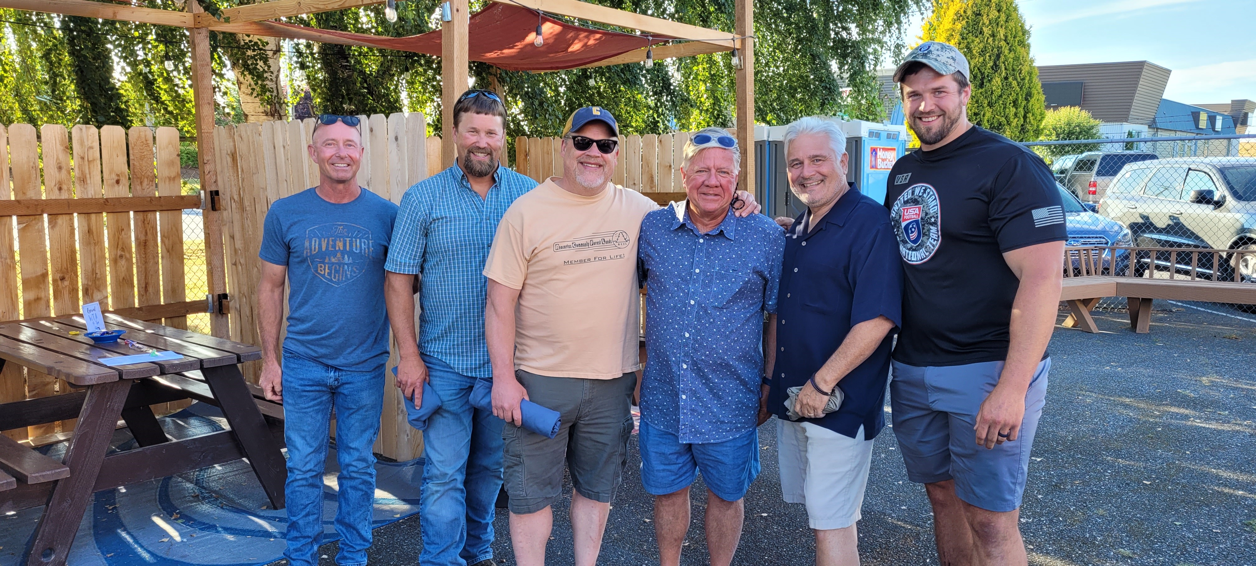 Six men standing together outside, in front of a wooden picnic table.